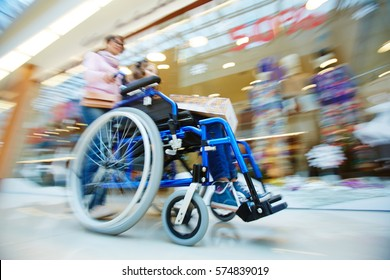 Woman pushing wheelchair with her daughter in the mall