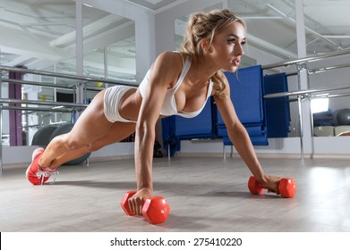 Woman push-ups on the floor at the gym