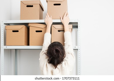 Woman put a cardboard box on a shelf of a rack in warehouse. Clean up and organize a pantry concept.