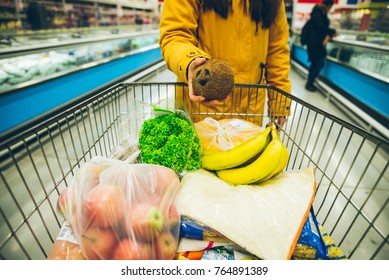 woman put cocnut in the cart with products in store