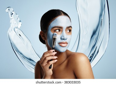 woman put facial mask, water splash on a background
