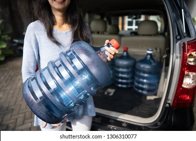 woman put a gallon of water in the car trunk at home. wanted to purchase the refill or by the new one