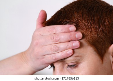 The woman put her hand to her forehead, experiencing a headache. Migraine, fever, blood pressure. Symptom of disease.