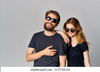 the woman put her hand on the man's shoulder in sunglasses