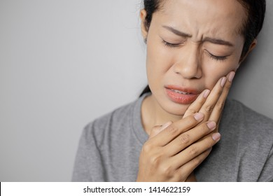 Woman put her hand on her cheek due to toothache. Asian  woman is suffering of toothache. Young woman with of toothache on a gray background.