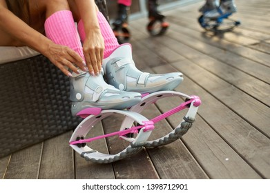 woman put on pink kangoo jumping boots before outdoor fitness workout