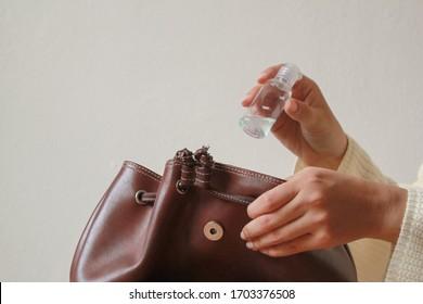 Une femme met du gel d'assainissement dans un sac.
