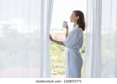 Woman put White bathrobe standing relax and drinking coffee morning at window in the