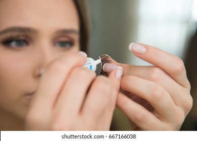 Woman puting cosmetic glue on fake eyelashes during makup