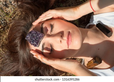 Woman puts amethyst stone on her forehead