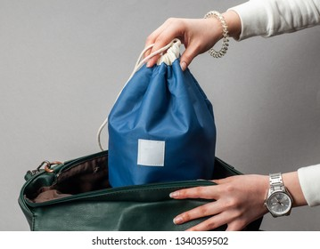 the woman puts the cosmetics bag