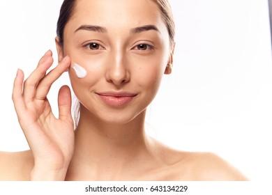 Woman puts cream on face