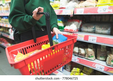 Woman puts the goods in the shopping basket. Shopping in a supermarket. Products in the red shopping basket.