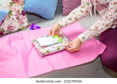 Woman puts a greeting card in a pink wrap sitting on a sofa. Gifts, holiday, new year, christmas.