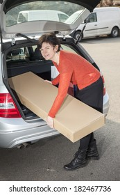 Woman puts her package in the car