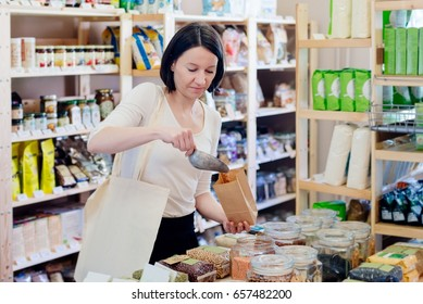 Woman puts lentil seeds into a paper bag in a healthy food store