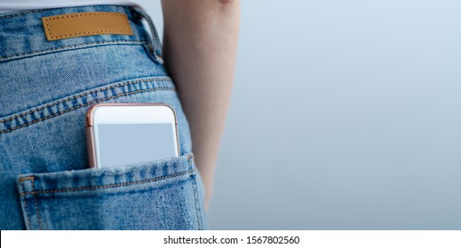 Woman puts mobile phone in jeans pocket on gray light background. Isolation, space for text