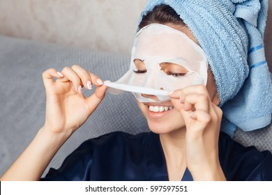 Woman puts nourishing mask on skin for rejuvenating and eliminating defects. Acne. Smile.