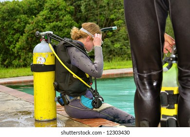 Woman puts on a mask while sitting in divers training pool. Shot in Sodwana Bay, KwaZulu-Natal province, Southern Mozambique area, South Africa.