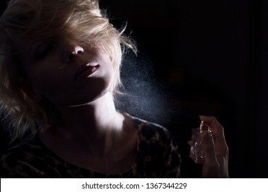 Woman puts on perfume on a dark background.