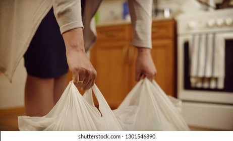 Woman puts packages on floor. Close-up of women's hands put on floor heavy bags of food at home. Food purchases for home