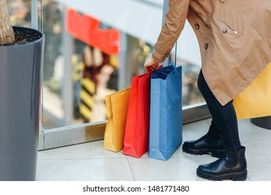Woman puts the packages on the floor in the shopping mall. The face is not visible. Buying too much concept.Time for shopping, copy space on the left side