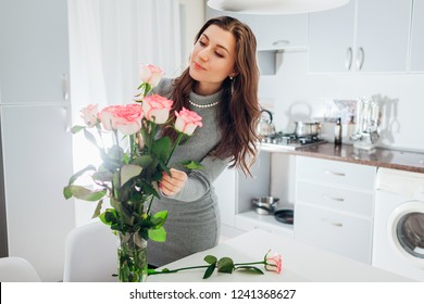 Woman puts roses in vase. Housewife taking care of coziness in kitchen. Modern kitchen design