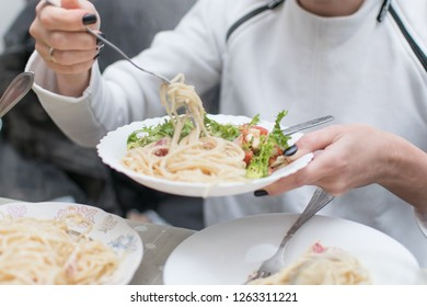 A woman puts spaghetti and fresh vegetable salad on a plate.