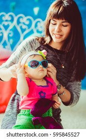 Woman puts sunglasses on the nose of charming little girl