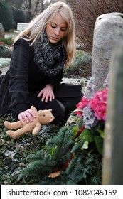 Woman puts a teddy bear on the grave of a deceased child in a graveyard in mourning over the loss