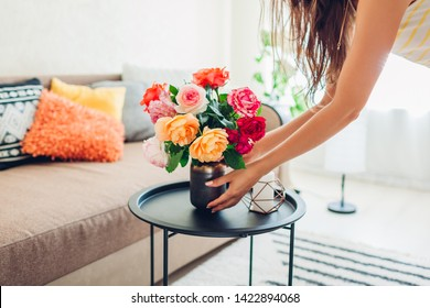 Woman puts vase with flowers roses on table. Housewife taking care of coziness in apartment. Interior design and decor