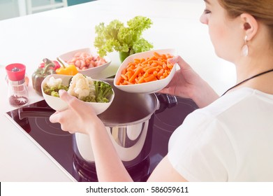 Woman puts vegetables into the pressure cooker. Conception of healthy nutrition.