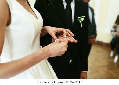 Woman puts wedding ring on groom's hand