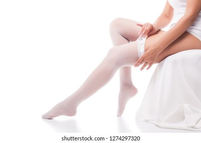 A woman puts a white stockings on her legs while sitting on a bed, white background, studio shooting.