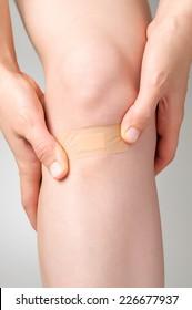 Woman putting an adhesive bandage on her leg