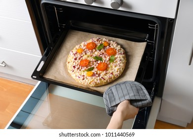 Woman putting baking sheet with pizza in oven