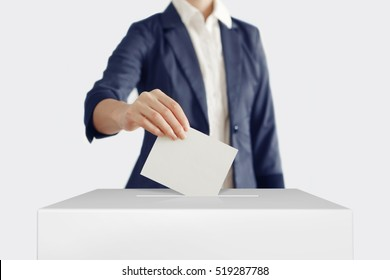 Woman putting a ballot into a voting box.