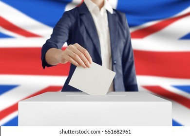 Woman putting a ballot into a voting box with British flag on background.