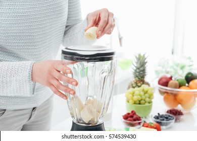 Woman putting a banana in a blender and preparing a delicious healthy smoothie in her kitchen