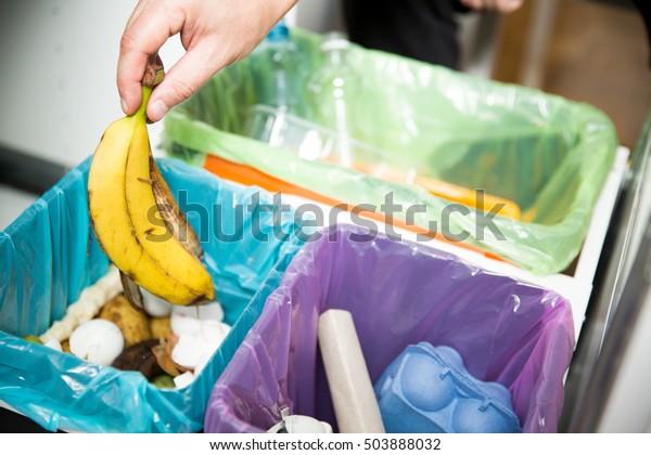 Frauen, die Bananenschale in die Küche versetzen, um Bio-bin zu recyceln. Person in der Hausküche, die Abfälle trennt. Verschiedene Mülltonne mit bunten Mülltüten.