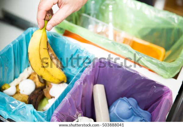 Mujer poniendo cáscara de plátano en el reciclaje de los bioscopios en la cocina. Persona en la cocina de la casa separando residuos. Diferentes botes de basura con coloridas bolsas de basura.