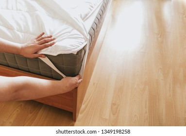 Woman is putting the bedding cover or mattress pad on the bed or putting off for cleaning process