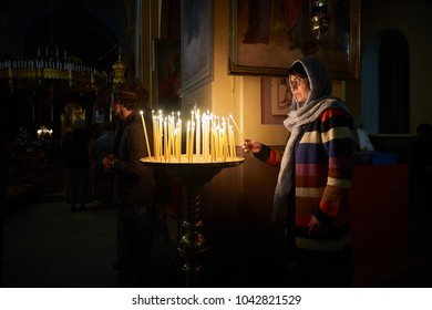 A woman is putting a candle and praying before candela in The Holy Trinity Cathedral of the Russian Orthodox Church in Jerusalem.