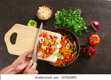 Woman putting chopped bell pepper with onion in saucepan, top view