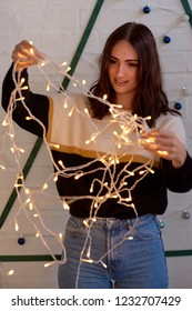 woman putting up christmas decorations with fairy lights, creative christmas tree crafting