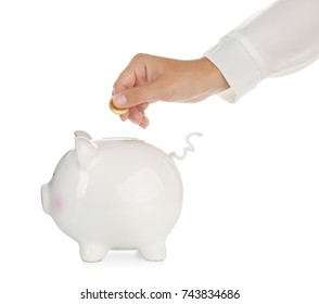 Woman putting coin into cute piggy bank against white background