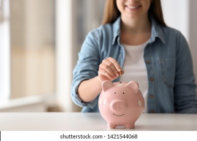Woman putting coin into piggy bank at table indoors, closeup. Space for text