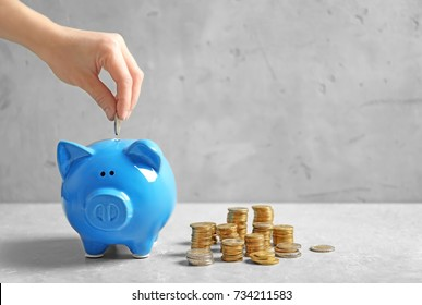 Woman putting coin into piggy bank on grey background. Saving money concept