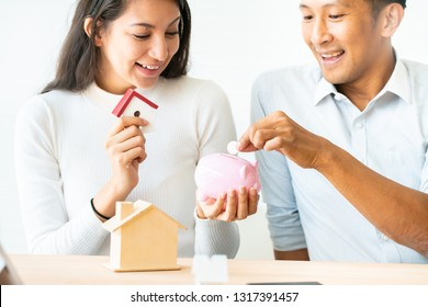 woman putting a coin into a pink piggy bank concept for savings and finance.The best choice of house.House owner and architect discussing a choice.Couple dreaming of new home.