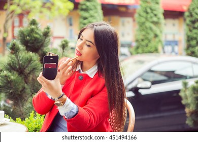 Woman putting, correcting red lipstick lip gloss. Coffee shop restaurant urban outdoors background. Mixt race model